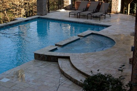 moon shaped spa attached to pool