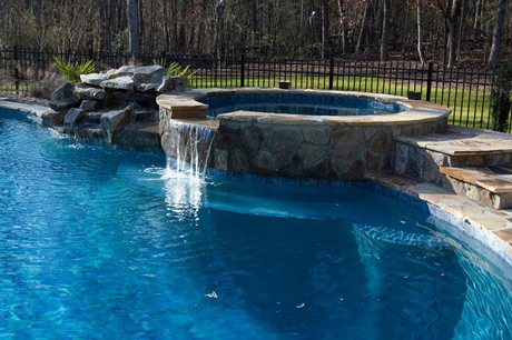 spa with waterfall into pool